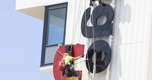 high rise sign installation using ropes