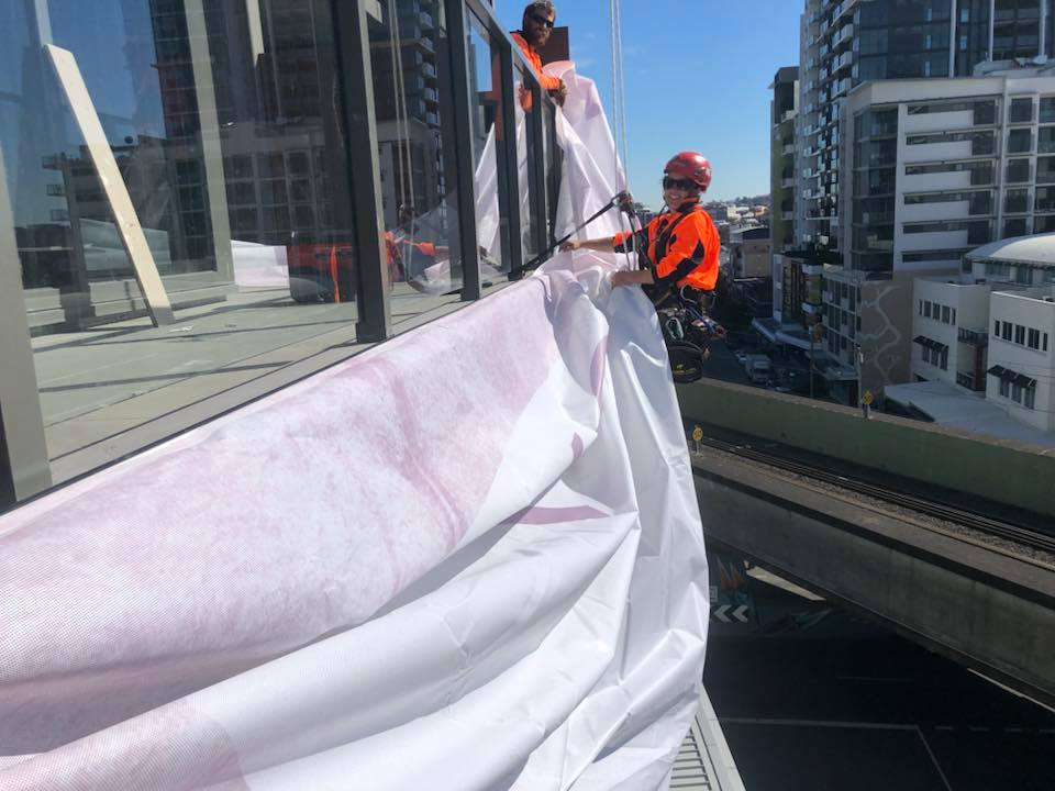 Rope Access Signage Installation - hanging large banners from Apartment building