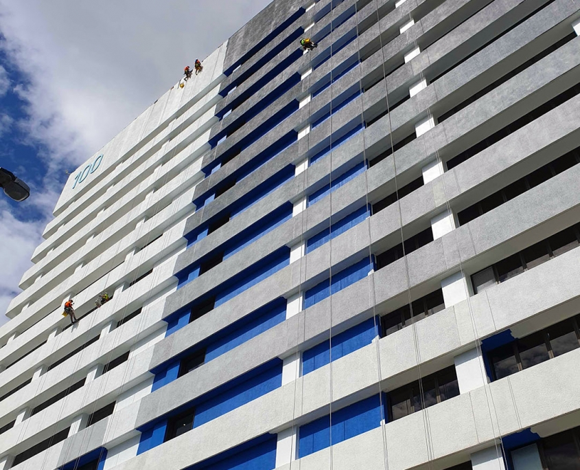 several rope access painters painting a high rise building in Brisbane