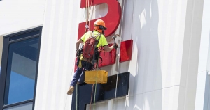 rope access technician installing sign